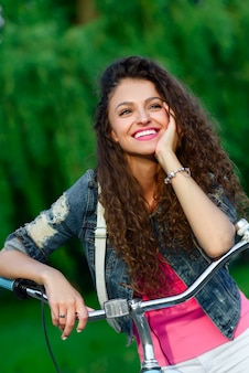 Beautiful girl with curly hair riding on a bicycle in the park in the summer in the city.