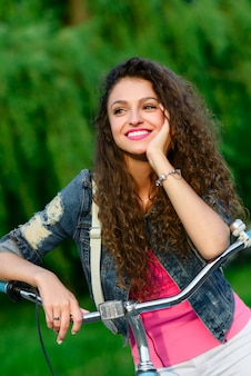 Beautiful girl with curly hair riding on a bicycle in the park in the summer in the city