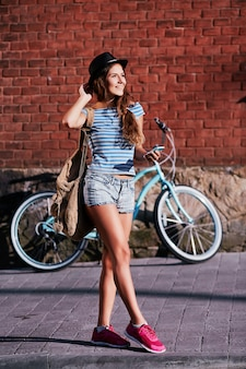 모자, 위쪽 및 자전거와 함께 서 있고 휴대 전화를 들고, 여행, 초상화 반바지를 입고 곱슬 머리를 가진 아름 다운 소녀.