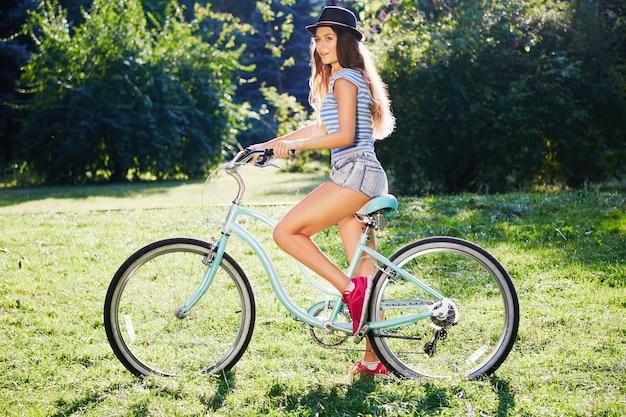 모자, 위쪽 및 공원에서 자전거와 함께 서있는 반바지, 여행, 초상화를 입고 곱슬 머리를 가진 아름 다운 소녀.