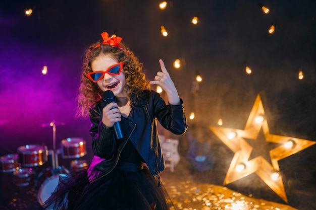 Beautiful girl with curly hair wearing leather jacket and red sunglasses sings into a wireless microphone for karaoke in recording studio