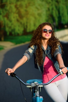 Beautiful girl with curly hair wearing sunglasses riding on a bicycle in the park in the summer in the city