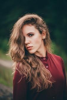 곱슬 자연 머리를 가진 아름 다운 소녀는 숲에서 자연을 즐길 수 있습니다. 녹색 배경에 와인 색 드레스에서 몽 상가 여자입니다. 영감을받은 소녀. 여성 얼굴 초상화입니다. 가을 머리에 태양. 빈티지 초상화.
