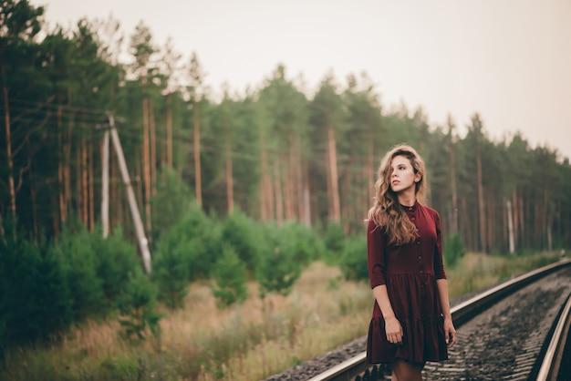 곱슬 자연 머리를 가진 아름 다운 소녀 철도 숲에서 자연을 즐길 수