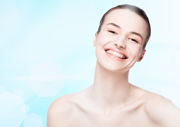 Beautiful girl with cute smile natural makeup spa skin care portrait on blue bokeh background