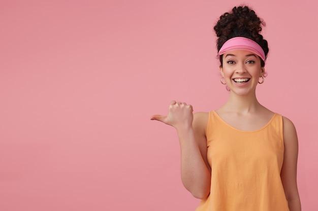 暗い巻き毛のお団子を持つ美しい少女。ピンクのバイザー、イヤリング、オレンジのタンクトップを着ています。補う