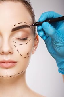 Красивая девушка с темными бровями на фоне студии, руки доктора в синих перчатках, рисуя линии перфорации на лице.