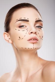 Красивая девушка с темными бровями на фоне студии с линиями перфорации на лице, концепция пластической хирургии, крупным планом портрет.