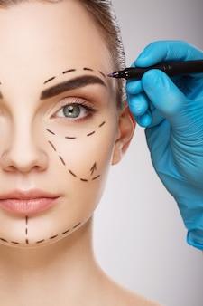 Красивая девушка с темными бровями у стены, руки доктора в синих перчатках, рисуя линии перфорации на лице.
