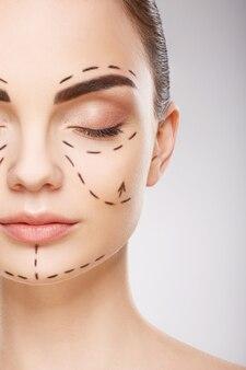 Красивая девушка с темными бровями на стене с линиями перфорации на лице, концепция пластической хирургии, крупным планом портрет.