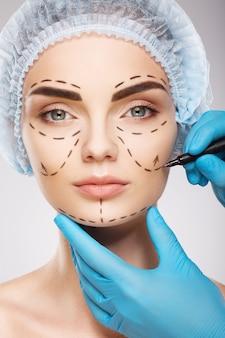 Красивая девушка с темными бровями в синей медицинской шляпе на фоне студии, руки врача в синих перчатках, рисуя линии перфорации на лице.