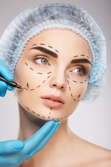 Beautiful girl with dark eyebrows wearing blue medical hat at studio background, doctor's hands wearing blue gloves drawing perforation lines on face.