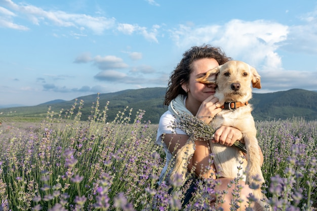Beautiful girl with dog on a lavender field