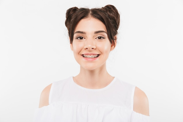Beautiful girl with double buns hairstyle and dental braces smiling in happy mood, isolated on white