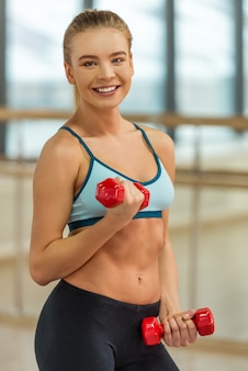 Beautiful girl with dumbbells smiling.