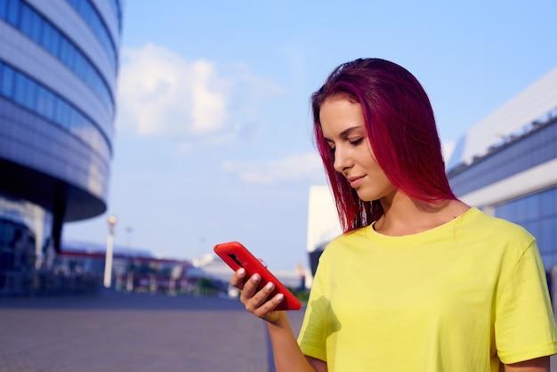 염색된 분홍색 머리와 밝은 옷을 입은 아름다운 소녀가 전화를 본다
