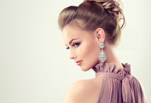 Beautiful girl with elegant hairstyle and big earrings jewelry