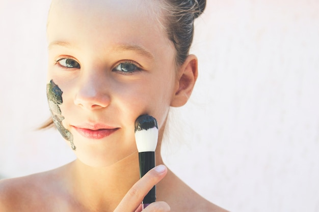 Beautiful girl with facial black clay mask