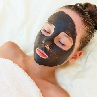 Beautiful girl with facial black clay mask.