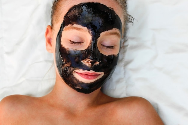 Beautiful girl with facial black mask.