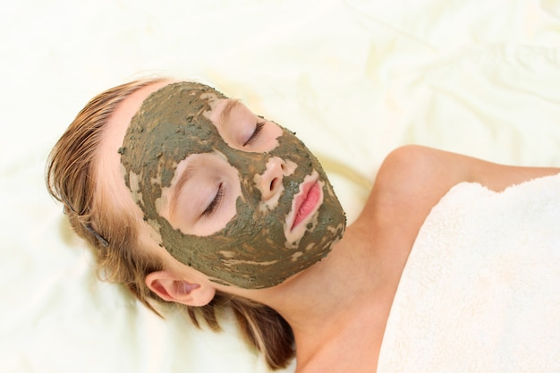 Beautiful girl with facial clay mask.