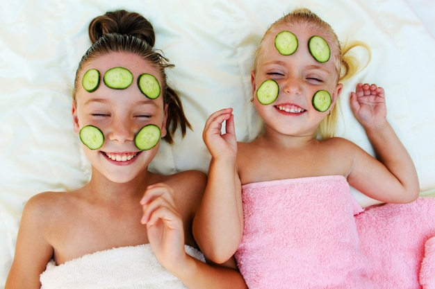 Beautiful girl with facial mask of cucumber. top view.