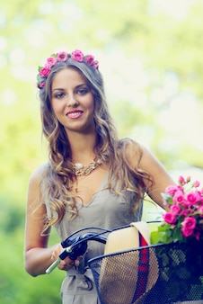 Beautiful girl with flowers on a bike