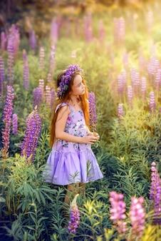 Красивая девушка с цветами в ее волосы среди цветов. солнечное летнее фото с ребенком в фиолетовых цветах