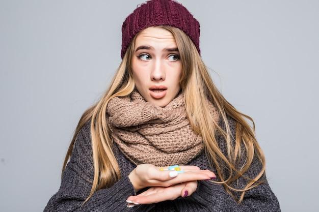 독감이나 감기에 걸린 아름다운 소녀는 회색으로 건강해지기 위해 약을 많이 복용합니다.