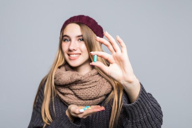 Красивая девушка с гриппом или простудой должна принять много таблеток, чтобы стать здоровой на сером