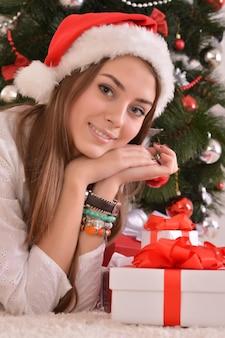 サンタ帽子のクリスマスツリーの近くに贈り物を持つ美しい少女