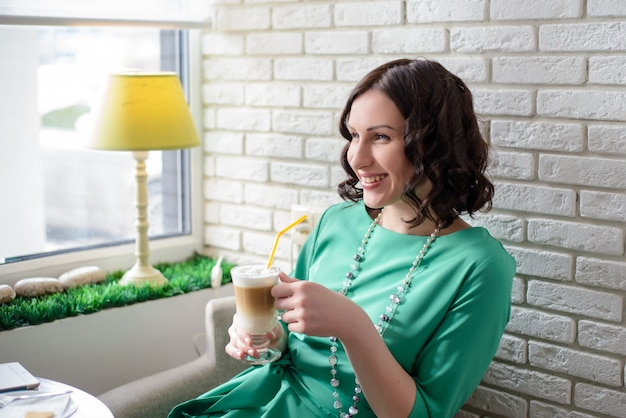 Beautiful girl with glass of coffee in a green dress