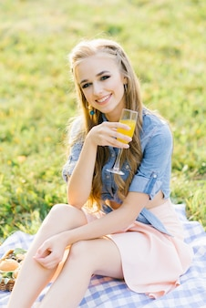 A beautiful girl with a glass of freshly squeezed juice sits on a blanket at a summer picnic and smiles a charming smile