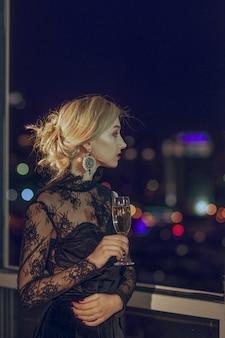 Красивая девушка с бокалом шампанского стоит возле окна с размытым ночной город