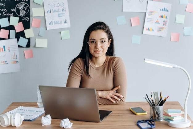 Красивая девушка в очках, работает за столом с ноутбуком