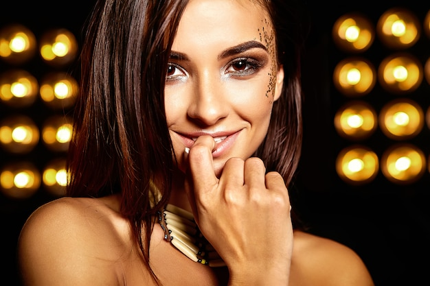 Beautiful girl with golden glitter on the face
