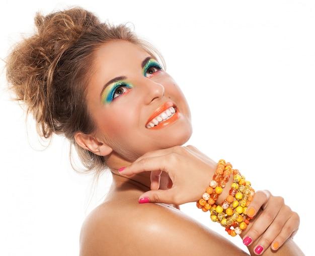 Красивая девушка с браслетом ручной работы и художественным макияжем