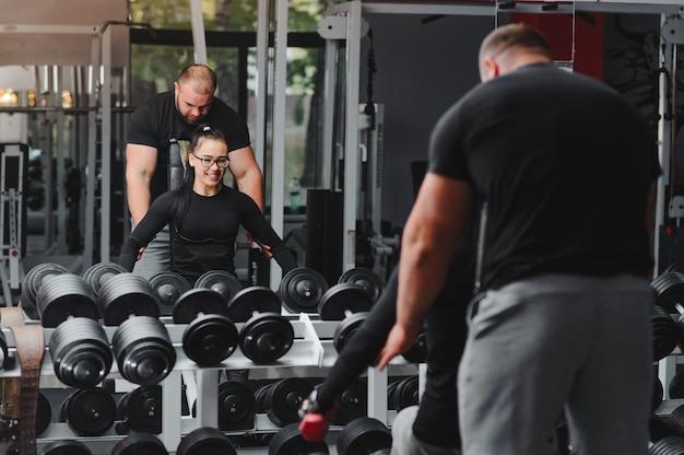 Красивая девушка с руками на гантелях, глядя на свое отражение в зеркале в спортивном зале. стройная молодая женщина принимает гантели перед зеркалом в фитнес-клубе.