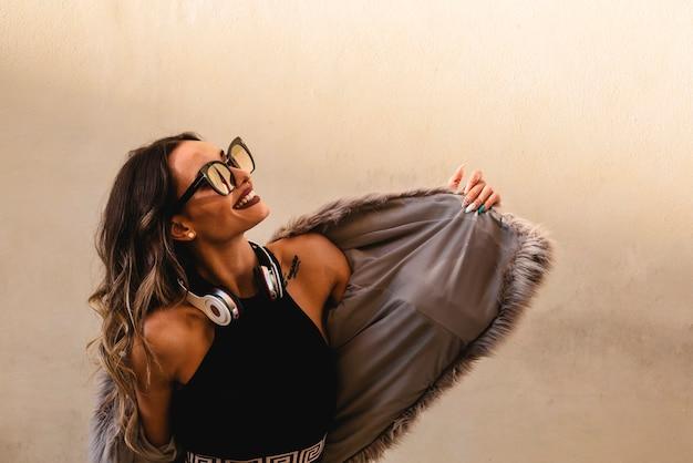 ヘッドフォンで美しい少女は音楽を聴き、屋外で踊ります。白い壁の背景