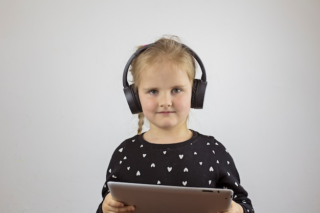 Beautiful girl with headphones and with a tablet looks into the camera
