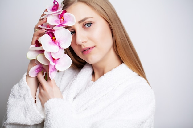 Beautiful girl with healthy skin and branch orchid