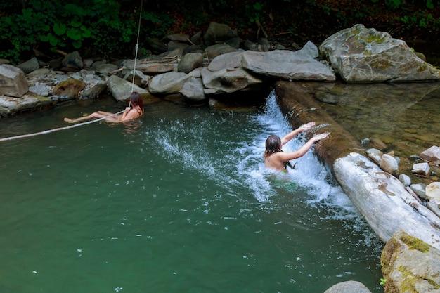 Красивая девушка с дочерью, купание в реке