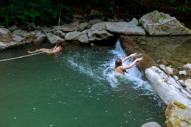 Beautiful girl with her daughter swimming in the river