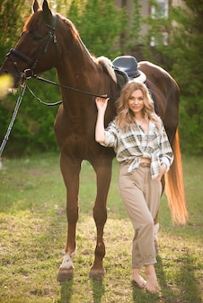 Beautiful girl with her horse and beautiful warm sunset in the spring forest.