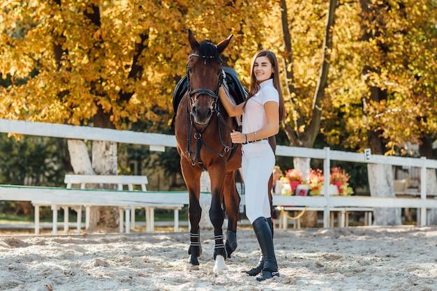 秋の森を一緒に歩いている茶色の馬と美しい少女。
