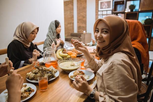 Красивая девушка с хиджабом улыбается и смотрит в камеру, когда ест быстро