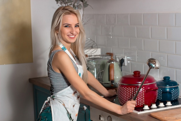 Beautiful girl with a ladle and an apron in the kitchen near the stove Premium Photo