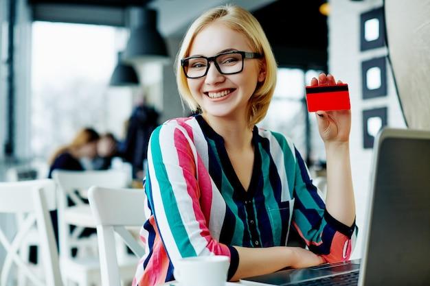 화려한 셔츠와 노트북 및 신용 카드, 프리랜서 개념, 온라인 쇼핑, 미소와 카페에 앉아 안경을 쓰고 가벼운 머리를 가진 아름 다운 소녀.