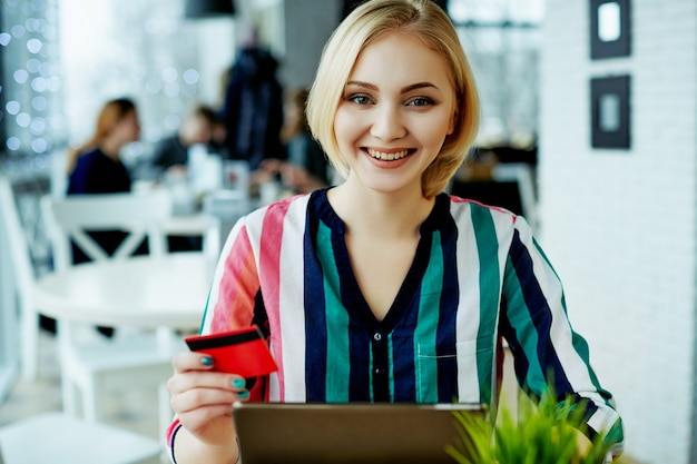 Beautiful girl with light hair wearing colorful shirt sitting in cafe with tablet, credit card and cup of coffee, freelance concept, online shopping.