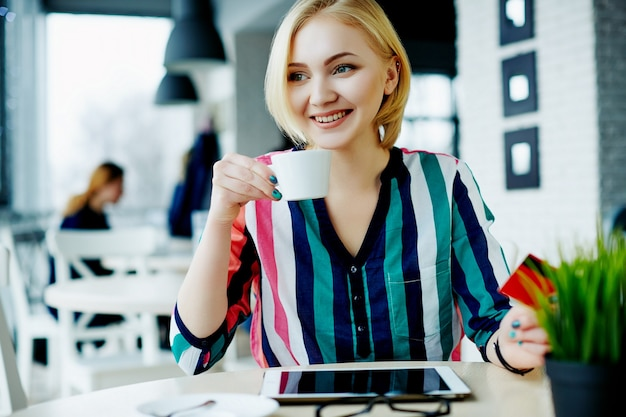 Beautiful girl with light hair wearing colorful shirt sitting in cafe with tablet, mobile phone and cup of coffee, freelance concept, online shopping.